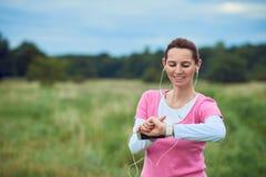 Μέσης ηλικίας γυναίκα που ελέγχει τον αθλητισμό ή το ρολόι υγείας της Στοκ φωτογραφίες με δικαίωμα ελεύθερης χρήσης