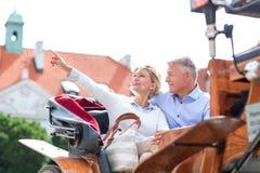Μέσης ηλικίας γυναίκα που παρουσιάζει κάτι στον άνδρα καθμένος στο κάρρο αλόγων Στοκ φωτογραφία με δικαίωμα ελεύθερης χρήσης