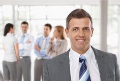 Μέσης ηλικίας επιχειρηματίας μπροστά από τους συναδέλφους στοκ εικόνα