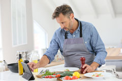 Μέσης ηλικίας μαγείρεμα ατόμων στην κουζίνα Στοκ φωτογραφία με δικαίωμα ελεύθερης χρήσης