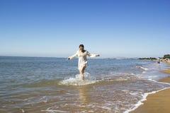 Μέσης ηλικίας τρεξίματα γυναικών στο νερό θαλασσίως Στοκ εικόνα με δικαίωμα ελεύθερης χρήσης