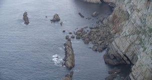 Μέση άποψη μιας βάσης απότομων βράχων με τη θάλασσα που χτυπά τους βράχους φιλμ μικρού μήκους