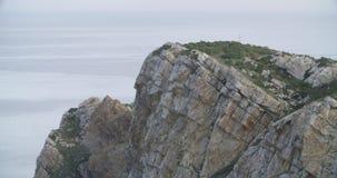 Μέση άποψη της κορυφής του απότομου βράχου με τη θάλασσα στην ηρεμία στον ορίζοντα φιλμ μικρού μήκους
