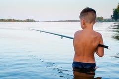 Μέση αλιείας αγοριών βαθιά στο νερό στοκ εικόνα με δικαίωμα ελεύθερης χρήσης