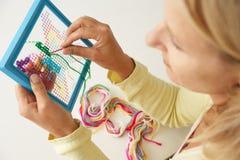 Μέση γυναίκα ηλικίας που κάνει τη διαγώνια βελονιά Στοκ φωτογραφία με δικαίωμα ελεύθερης χρήσης