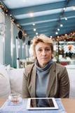 Μέση γυναίκα ηλικίας με τον καφέ συνεδρίασης ταμπλετών Στοκ Φωτογραφία