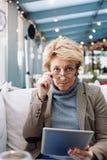 Μέση γυναίκα ηλικίας με τον καφέ συνεδρίασης ταμπλετών Στοκ Εικόνα