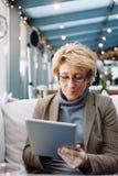 Μέση γυναίκα ηλικίας με τον καφέ συνεδρίασης ταμπλετών Στοκ Εικόνες