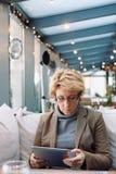 Μέση γυναίκα ηλικίας με τον καφέ συνεδρίασης ταμπλετών Στοκ εικόνα με δικαίωμα ελεύθερης χρήσης