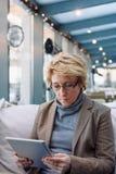 Μέση γυναίκα ηλικίας με τον καφέ συνεδρίασης ταμπλετών Στοκ Φωτογραφίες