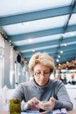 Μέση γυναίκα ηλικίας με τον καφέ τηλεφωνικής συνεδρίασης κυττάρων Στοκ Φωτογραφία