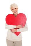 Μέση γυναίκα ηλικίας που αγκαλιάζει την καρδιά Στοκ Εικόνα