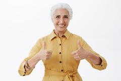 Μέση-επάνω στον πυροβολισμό η καλή και συμπαθητική κομψή ηλικιωμένη κυρία στο καθιερώνον τη μόδα κίτρινο παλτό που παρουσιάζει αν στοκ φωτογραφίες με δικαίωμα ελεύθερης χρήσης