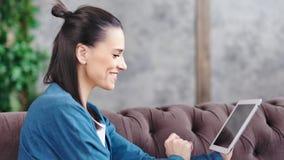 Μέση ευτυχής όμορφη νέα γυναίκα κινηματογραφήσεων σε πρώτο πλάνο που χαμογελά και που κοιτάζει στην οθόνη του PC ταμπλετών φιλμ μικρού μήκους