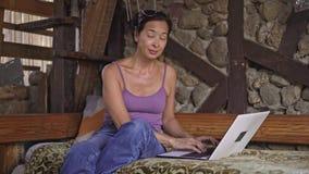 Μέση ηλικίας ασιατική δακτυλογράφηση γυναικών στο lap-top στο σπίτι απόθεμα βίντεο