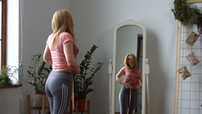 Μέση ηλικίας γυναίκα που μετρά τη μέση της με την ταινία φιλμ μικρού μήκους