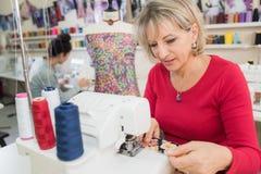 Μέση ηλικίας γυναίκα που χρησιμοποιεί τη ράβοντας μηχανή Στοκ φωτογραφία με δικαίωμα ελεύθερης χρήσης