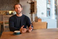 Μέση ηλικίας καυκάσια αρσενική συνεδρίαση στον πίνακα στη καφετερία που εξηγεί την ουσία στοκ εικόνα με δικαίωμα ελεύθερης χρήσης
