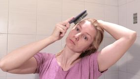 Μέση ηλικίας ξανθή γυναίκα που βουρτσίζει την υγρή τρίχα της με ένα brusher τρίχας στο λουτρό φιλμ μικρού μήκους