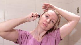 Μέση ηλικίας ξανθή γυναίκα που βουρτσίζει την υγρή τρίχα της με ένα brusher τρίχας στο λουτρό απόθεμα βίντεο