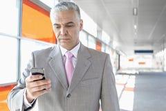 Μέση ηλικίας αποστολή κειμενικών μηνυμάτων επιχειρηματιών μέσω του τηλεφώνου κυττάρων στο σταθμό σιδηροδρόμου Στοκ Εικόνες