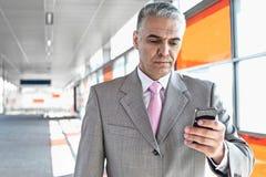 Μέση ηλικίας αποστολή κειμενικών μηνυμάτων επιχειρηματιών μέσω του τηλεφώνου κυττάρων στο σταθμό σιδηροδρόμου Στοκ Φωτογραφία