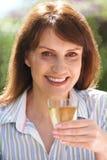 Μέση ηλικίας γυναίκα που απολαμβάνει το ποτήρι του άσπρου κρασιού Στοκ Εικόνες