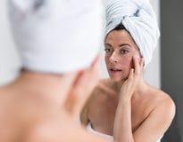 Μέση ηλικίας γυναίκα που εξετάζει την στον καθρέφτη Στοκ Φωτογραφία