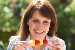 Μέση ηλικίας γυναίκα που τρώει τα φρούτα Kebab στον κήπο Στοκ φωτογραφία με δικαίωμα ελεύθερης χρήσης