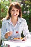 Μέση ηλικίας γυναίκα που τρώει το κύπελλο των φρούτων στον κήπο Στοκ Εικόνες