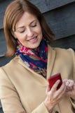 Μέση ηλικίας γυναίκα που χρησιμοποιεί το τηλέφωνο κυττάρων στοκ εικόνες