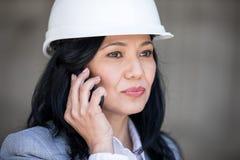 Μέση ηλικίας επιχειρηματίας στο σκληρό καπέλο που μιλά στο smartphone και που κοιτάζει μακριά Στοκ εικόνες με δικαίωμα ελεύθερης χρήσης