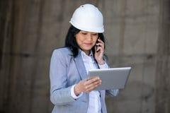 Μέση ηλικίας επιχειρηματίας στο σκληρό καπέλο που μιλά στο smartphone και που χρησιμοποιεί την ψηφιακή ταμπλέτα Στοκ Εικόνες