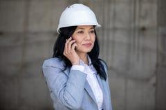 Μέση ηλικίας επιχειρηματίας στο σκληρό καπέλο που μιλά στο smartphone και που κοιτάζει μακριά Στοκ φωτογραφία με δικαίωμα ελεύθερης χρήσης