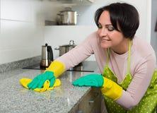 Μέση ηλικίας θηλυκή ξεσκονίζοντας κορυφή κουζινών Στοκ Εικόνες