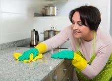 Μέση ηλικίας θηλυκή ξεσκονίζοντας κορυφή κουζινών Στοκ φωτογραφίες με δικαίωμα ελεύθερης χρήσης
