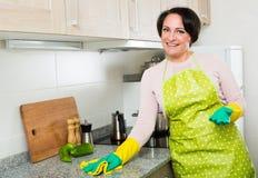 Μέση ηλικίας θηλυκή ξεσκονίζοντας κορυφή κουζινών Στοκ φωτογραφία με δικαίωμα ελεύθερης χρήσης