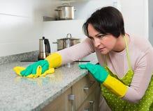 Μέση ηλικίας θηλυκή ξεσκονίζοντας κορυφή κουζινών Στοκ εικόνες με δικαίωμα ελεύθερης χρήσης