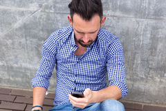 Μέση ηλικίας συνεδρίαση ατόμων εξωτερική και που χρησιμοποιεί το κινητό τηλέφωνο Στοκ εικόνα με δικαίωμα ελεύθερης χρήσης