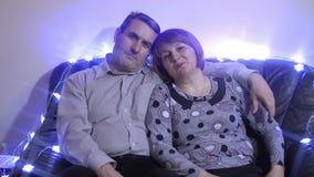 Μέση ηλικίας χαλάρωση ζευγών στον καναπέ που χαμογελά στη κάμερα στο σπίτι στο καθιστικό απόθεμα βίντεο