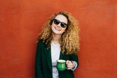 Μέση κινηματογράφηση σε πρώτο πλάνο της ευτυχούς όμορφης γυναίκας με τη σγουρή τρίχα που φορά τα γυαλιά ηλίου και το φλυτζάνι εκμ στοκ φωτογραφία