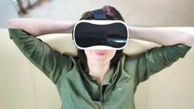 Μέση παρακαλεσμένη κινηματογράφηση σε πρώτο πλάνο γυναίκα που φορά τη σύγχρονη μάσκα και τη χαλάρωση εικονικής πραγματικότητας απόθεμα βίντεο