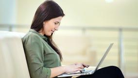 Μέση πυροβοληθείσα ενθουσιώδης εσωτερική νέα απόλαυση γυναικών που κουβεντιάζει χρησιμοποιώντας το PC lap-top φιλμ μικρού μήκους