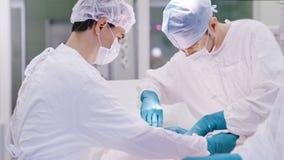 Μέση πυροβοληθείσα επαγγελματική ιατρική ομάδα που εκτελεί τη λειτουργία χειρουργικών επεμβάσεων στον ασθενή φιλμ μικρού μήκους
