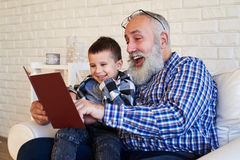 Μέση πλευρά που πυροβολείται του συνεπαρμένου granfather και του γιου του διαβάζοντας το s στοκ φωτογραφίες με δικαίωμα ελεύθερης χρήσης