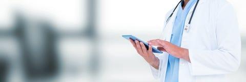Μέση ταμπλέτα εκμετάλλευσης τμημάτων γιατρών ενάντια στο μουτζουρωμένο γκρίζο γραφείο στοκ φωτογραφία με δικαίωμα ελεύθερης χρήσης