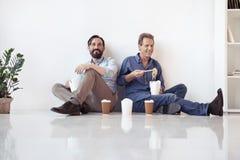 Μέσοι ηλικίας επιχειρηματίες που τρώνε τα ασιατικά τρόφιμα και που πίνουν τον καφέ καθμένος στο πάτωμα στην αρχή Στοκ Εικόνες