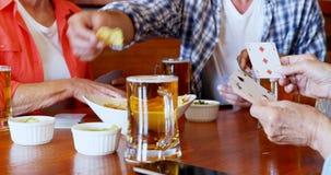 Μέσοι φίλοι τμημάτων που παίζουν τις κάρτες ενώ έχοντας την μπύρα και τα πρόχειρα φαγητά 4k απόθεμα βίντεο