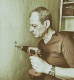 Μέσος-ενήλικη τρυπώντας με τρυπάνι τρύπα ατόμων στον τοίχο Έννοια κινηματογραφήσεων σε πρώτο πλάνο Στοκ φωτογραφίες με δικαίωμα ελεύθερης χρήσης