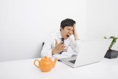 Μέσος ενήλικος επιχειρηματίας που κραυγάζει με το lap-top στο γραφείο στην αρχή Στοκ Εικόνες